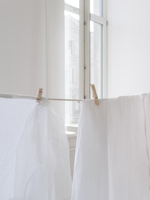 twee witte lakens drogen binnen aan de waslijn met twee houten knijpers