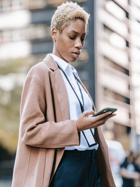 Business vrouw op straat kijkt naar haar telefoon