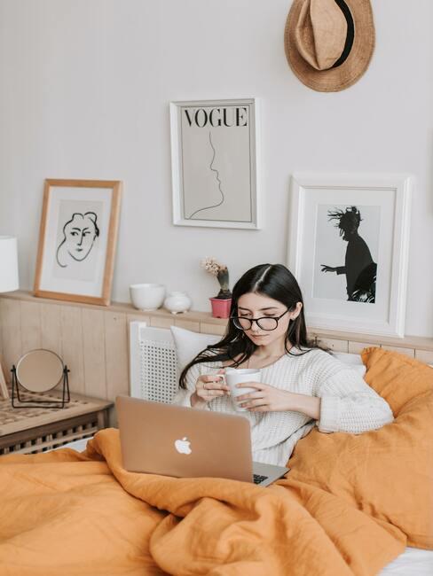 Vrouw drinkt kop koffie in bed en zit achter laptop