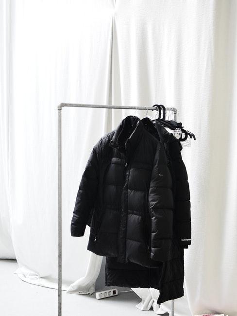 een lange herfstjas hangt aan een witte plastic hanger
