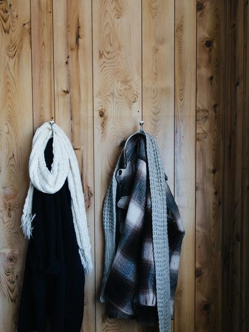 kleren hangen aan haken aan een houten muur
