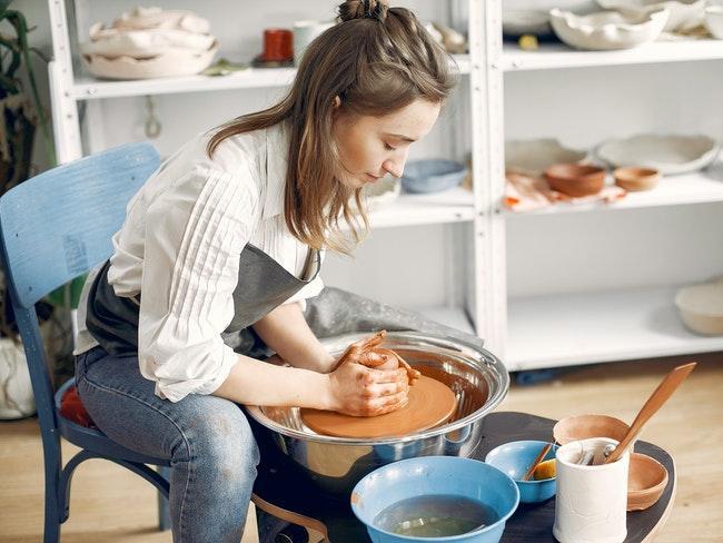 porselein schilderen: een vrouw maakt met de hand een aardewerken schaal
