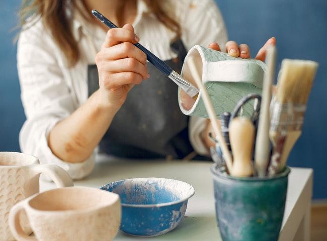 een vrouw schildert met de hand een aardewerken vat