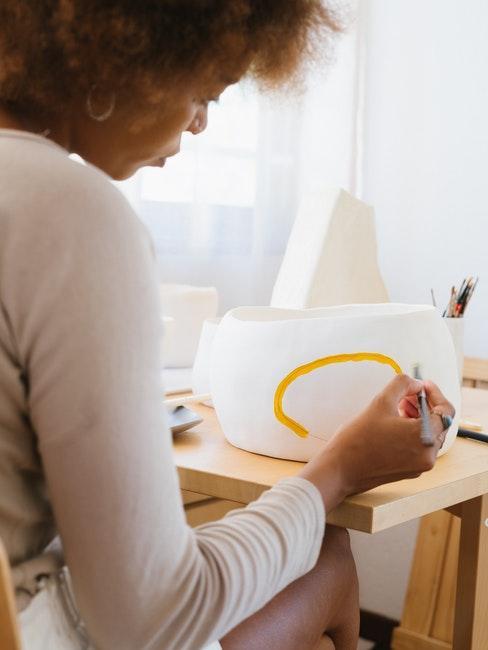vrouw schildert porselein met gele verf