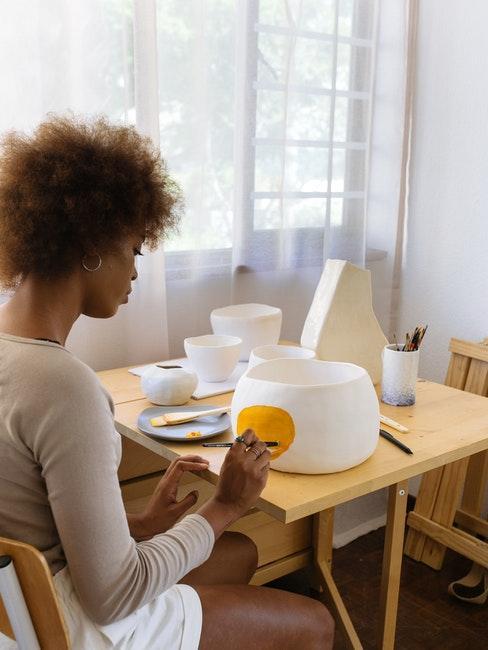 vrouw schildert wit porselein met oranje verf