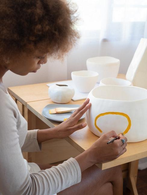 een vrouw schildert met de hand een porseleinen schaal