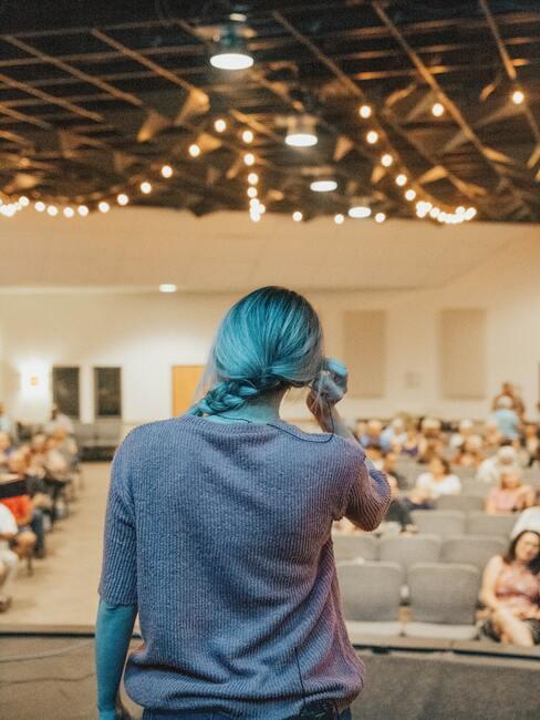 Vrouw staat voor grote zaal en gaat een speech geven