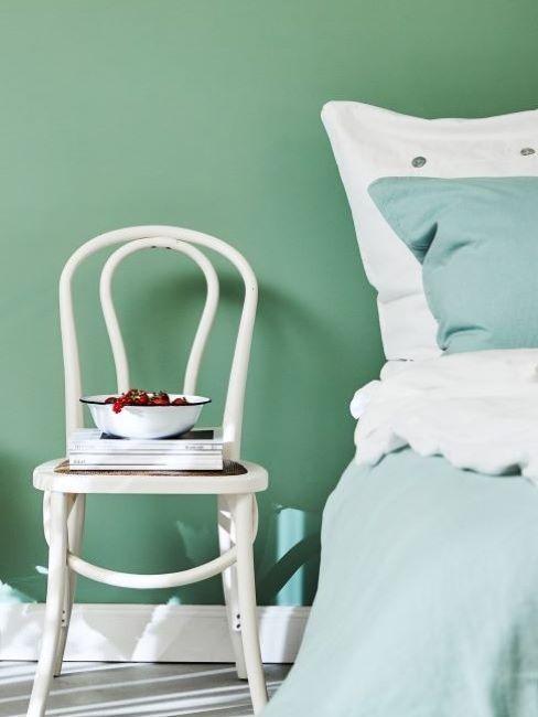 turkoois en wit beddengoed in een groene slaapkamer
