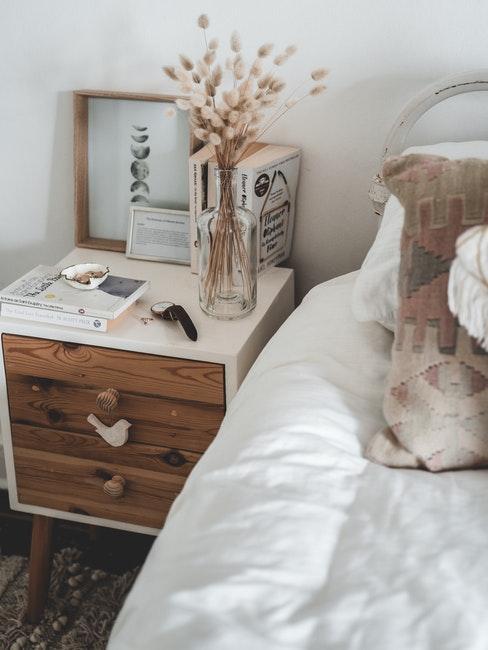 houten nachtkastje met een wit tafelblad naast het bed met wit linnen