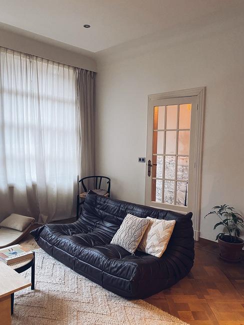 huiskamer van Liesbeth met zwarte organische bank