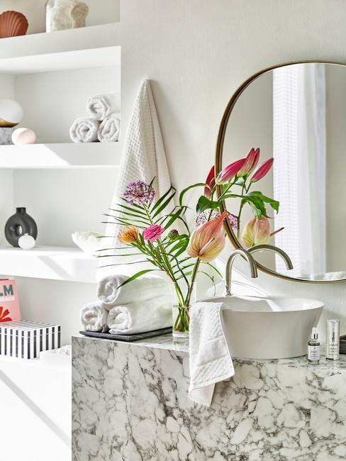 marmer badkamer meubel met ronde wasbak en ronde gouden spiegel