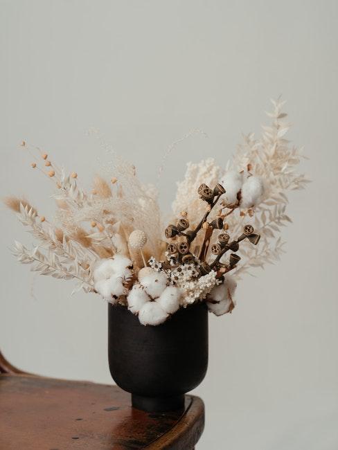 zwarte vaas van keramiek op een stoel met een boeket gedroogde bloemen