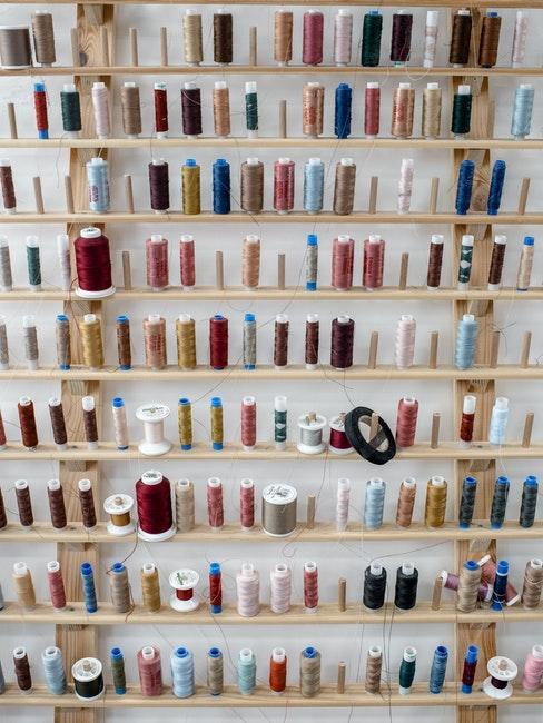 draden van verschillende kleuren op houten wandrek