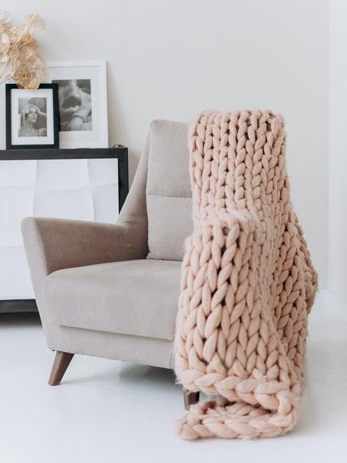 hand gebreide plaid in roze op fluwelen fauteuil