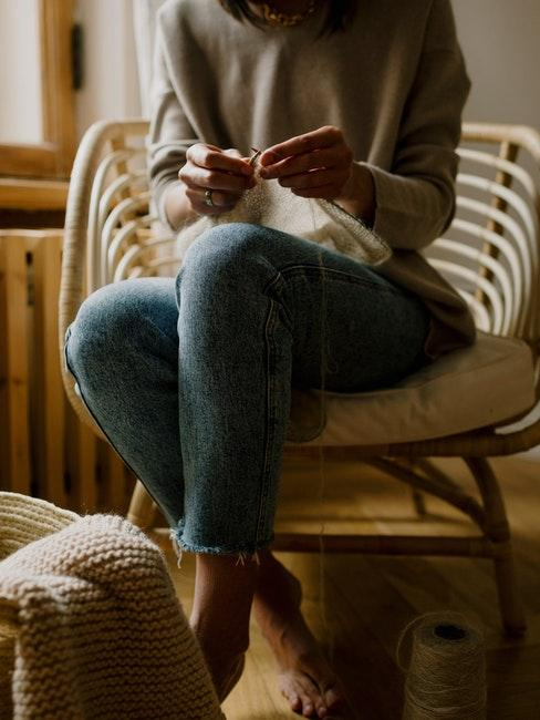 vrouw in een fauteuil breit een trui