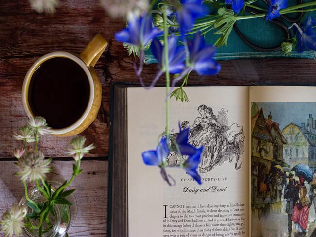 vers gesneden takken ridderspoor op een boek met een kop koffie op tafel