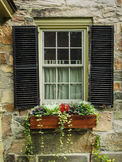 houten plantenbak bij raam met luiken