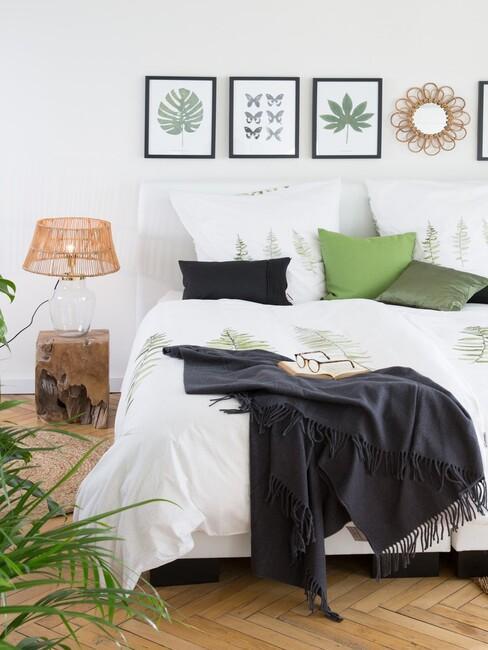 bed met posters in lijsten achter het bed