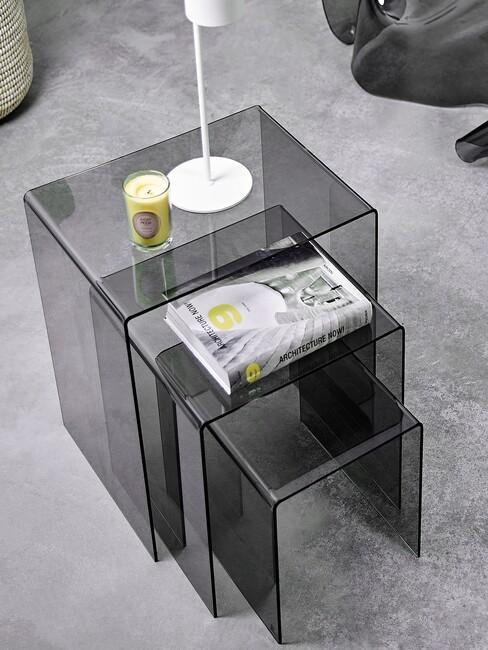 zwarte doorschijnende tafels op een licht grijs vloerkleed