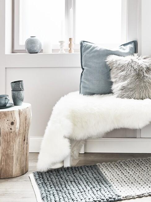 Bank met houten tafel blauw kussen en faux fur deken