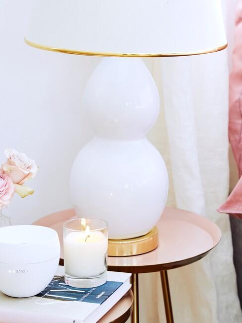 witte lamp met gouden accenten op een pastel roze bijzettafel