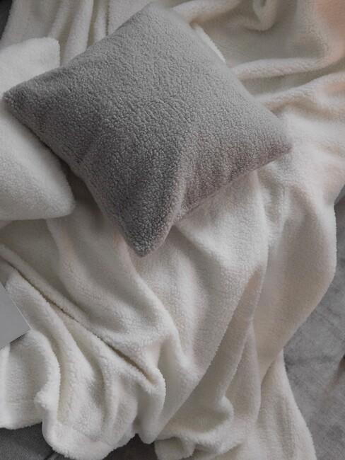 Witte deken met grijs kussen
