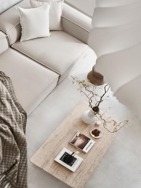 beige bank met houten tafel en witte lamp