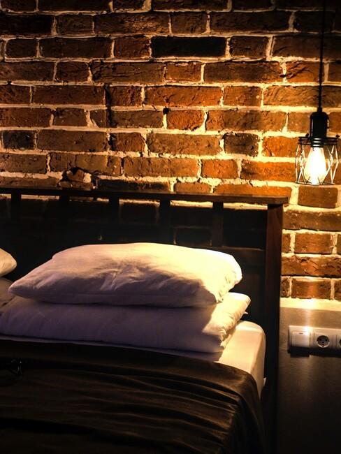 slaapkamer met een bakstenen muur en een zwart bed