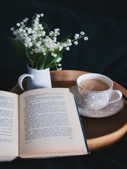Bloemen in de vaas op houten bijzettafel naast een kopje koffie en boek