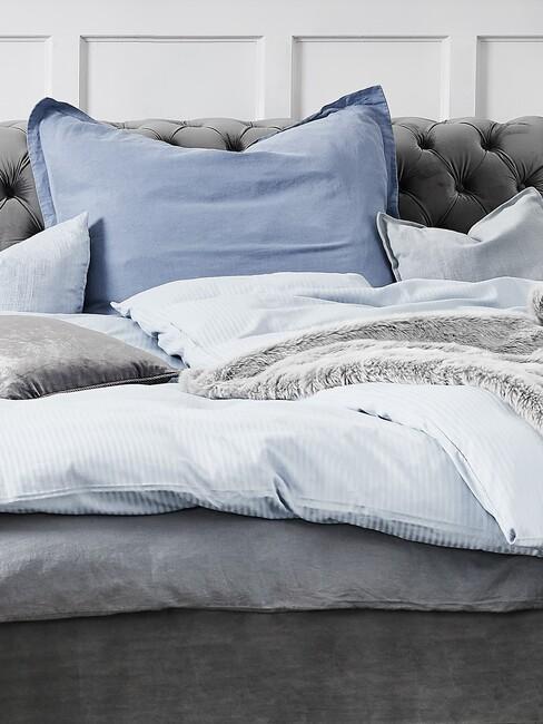 grijs bed met blauw kussen