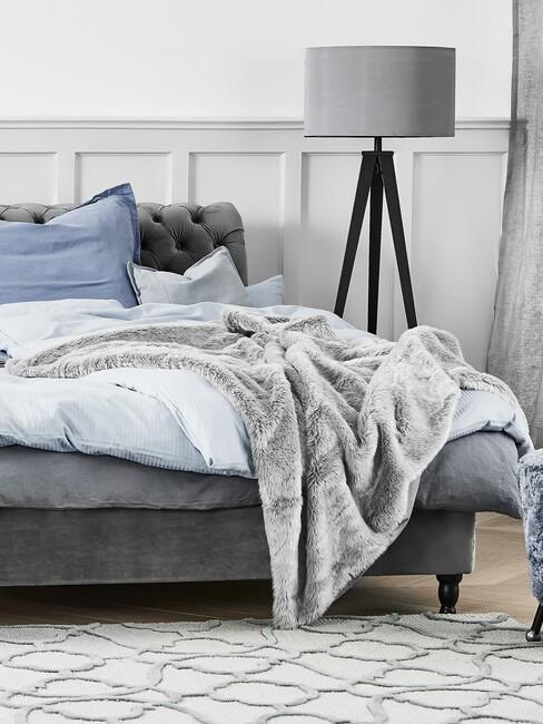 landelijke slaapkamer met blauwe deken