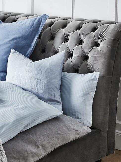 grijs bed met knopen en blauwe kussens