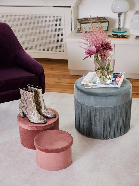 laarsen op roze poef en paarse stoel