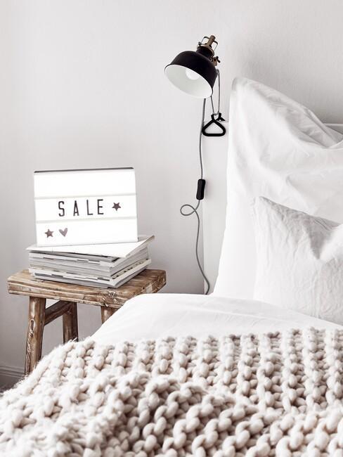 witte slaapkamer met zwarte lamp e beige deken