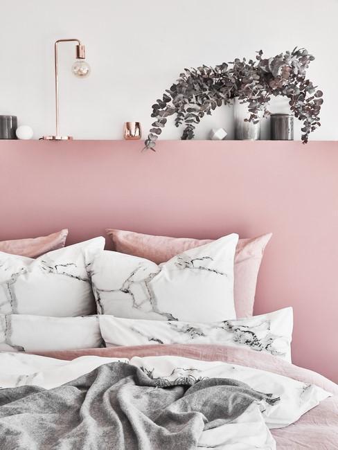 Roze slaapkamer met marmer dekbed en plant