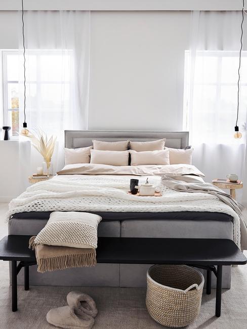 grijs bed met zwart bankje en wit dekbedovertrek