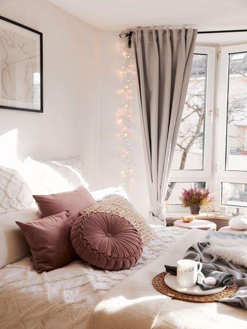 Witte kamer met roze kussens en raam met lampen