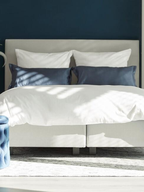 donkerblauwe slaapkamer met grijs bed witte lakens en blauwe kussens