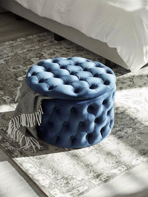 donkerblauwe kist met knopen op grijs kleed