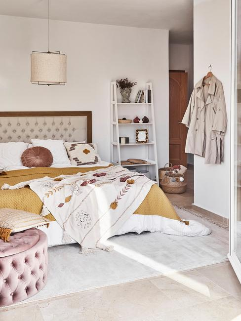 lichte slaapkamer met gele deken en roze poef