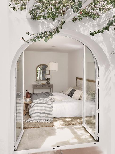 witte slaapkamer met grote openslaande deuren en grijze deken
