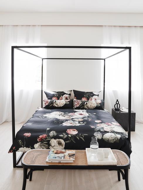 Zwart hemelbed met zwart dekbed met bloemen en bankje