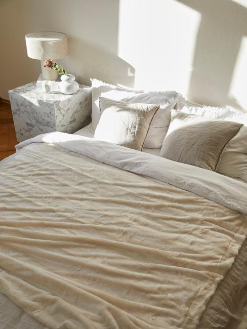 lichte kamer met wit dekbed en marmere tafel