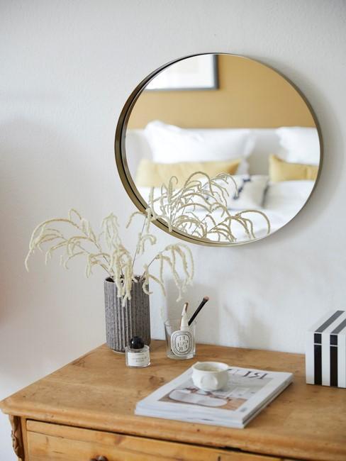 Ronde spiegel boven houten kast