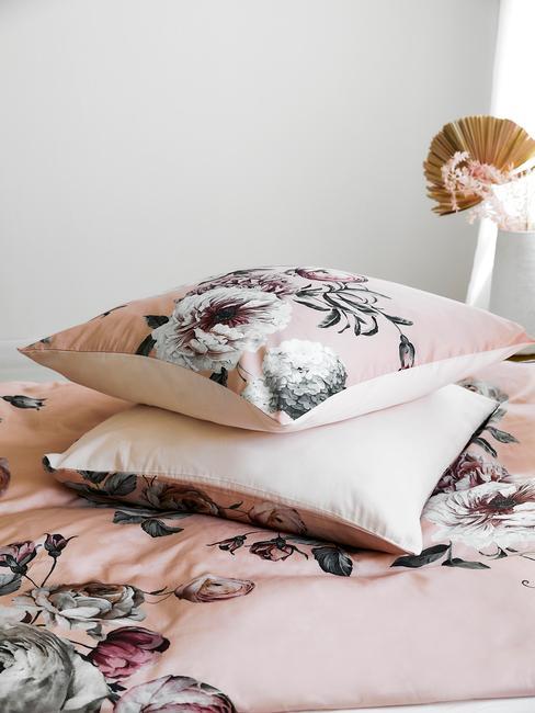 roze bloemenkussens op een bed