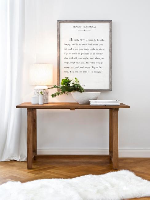 houten tafel met fotolijst en plant in witte vaas