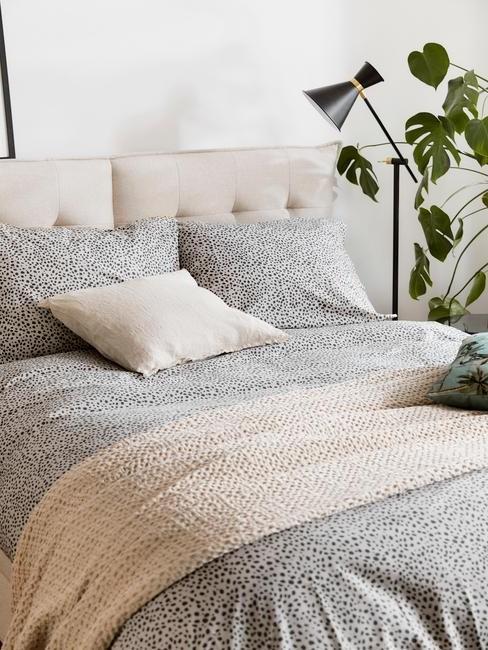 toupe bed met grijze deken en zwarte lamp