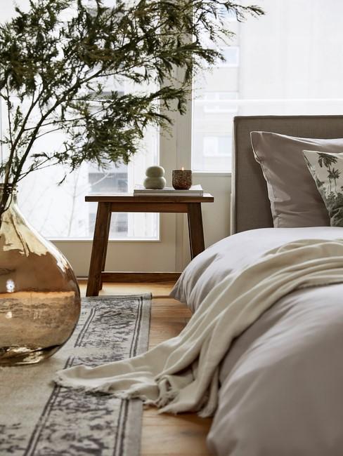 grijs dekbed met houten tafel en plant