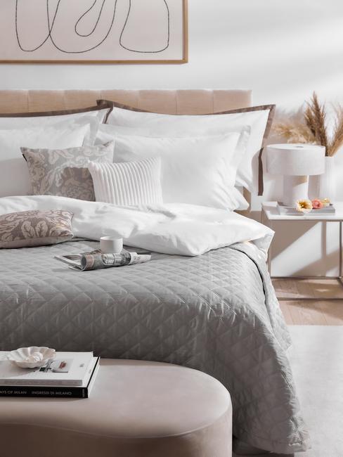 beige boxspring met wit dekbed en grijze deken
