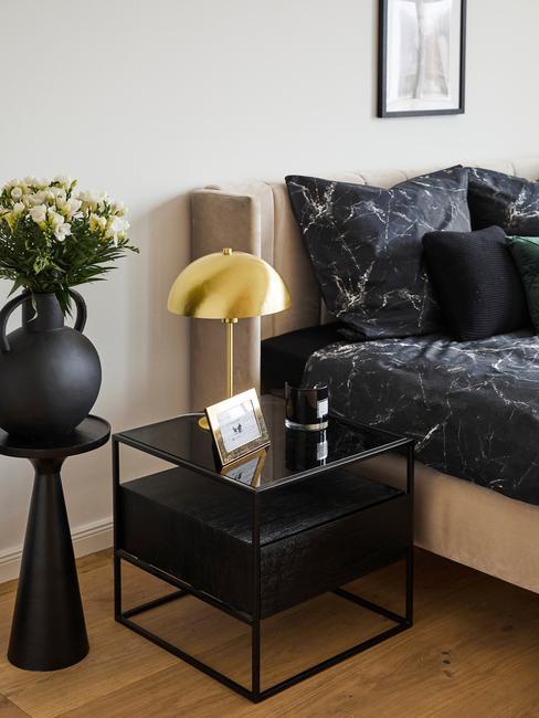 zwart nachtkastje met gouden lamp
